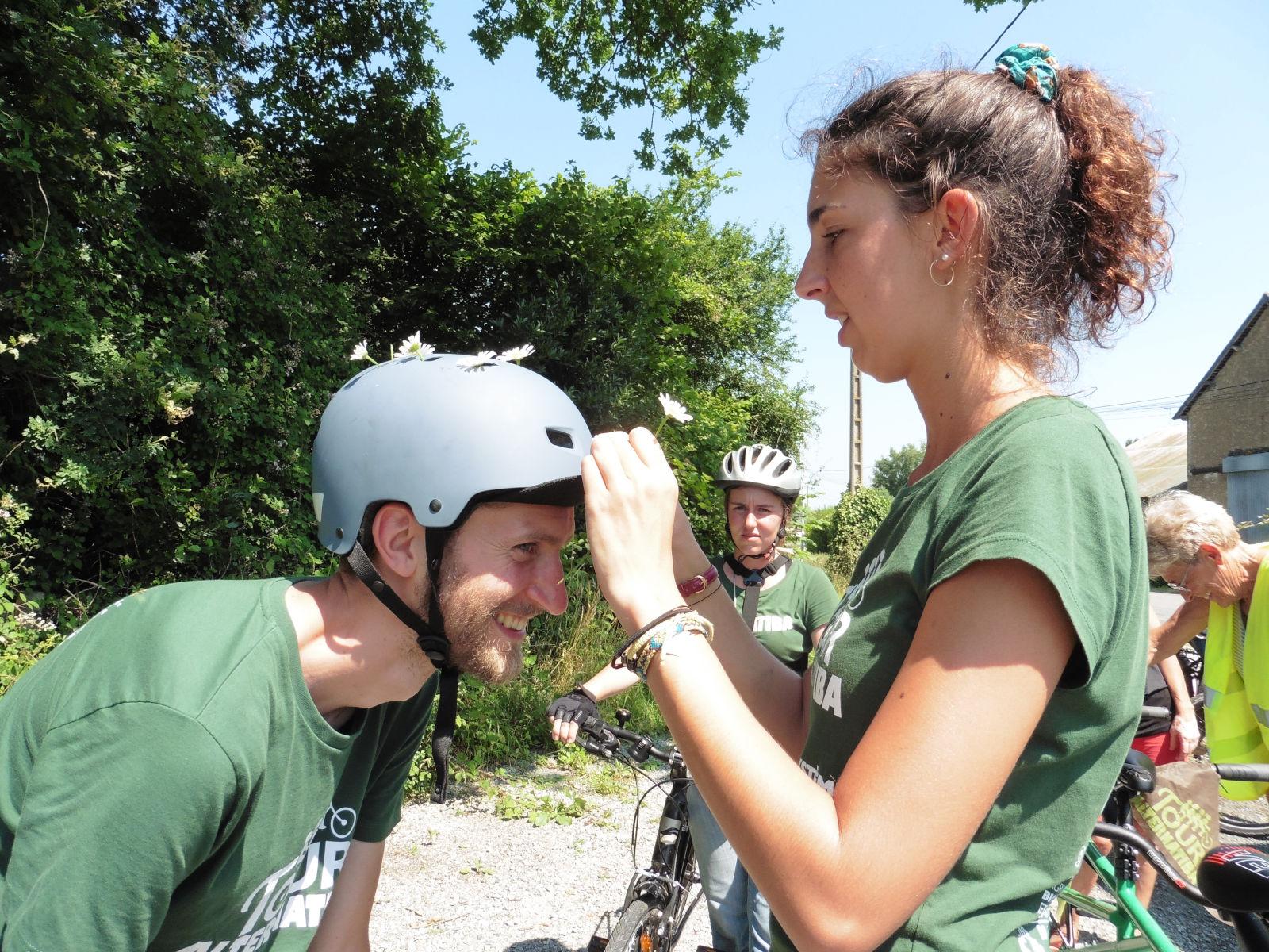 Tanika place des pâquerettes au casque d'un cycliste