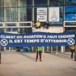 """Banderole : """"Climat ou aviation, il faut choisir. Il est temps d'atterir."""", """"RDV le 3 octobre, roulons sur Roissy"""""""