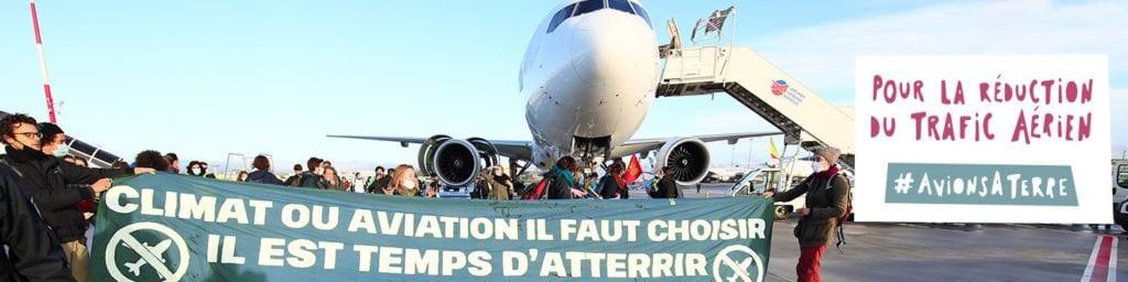 """Foule de militants devant un avion avec une banderole """"Climat ou aviation, il faut choisir. Il est temps d'atterrir"""". Pour la réduction du trafic aérien #AvionsATerre"""