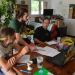 3 personnes travaillent autour d'une table